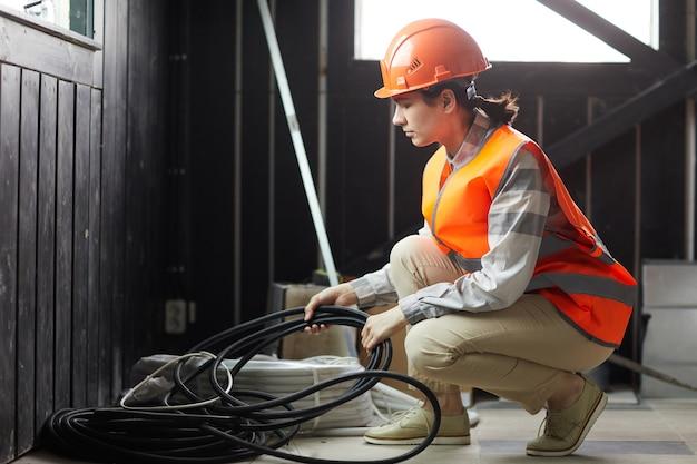 Молодая женщина в рабочем шлеме, принимая провода, она работает на строительной площадке