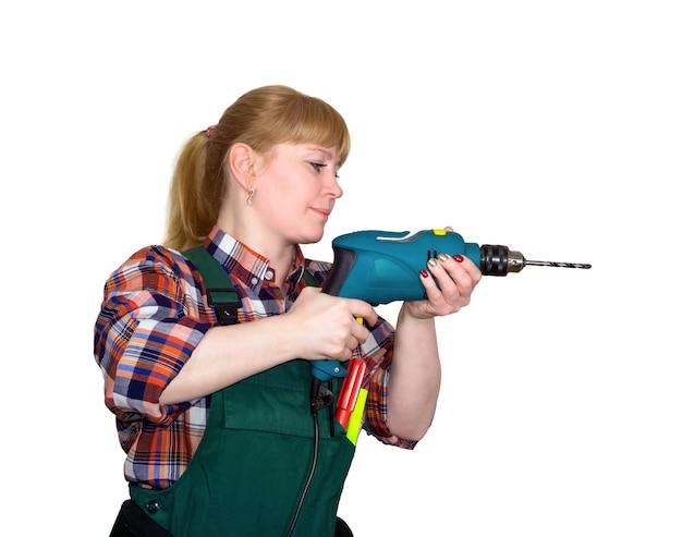 白い背景の上の手持ちのコード付き電気ドリルによる掘削作業オーバーオールの若い女性