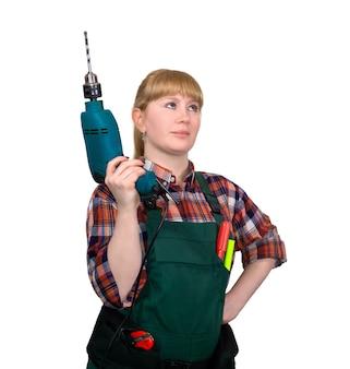 ハンドヘルドコード付き電気ドリルを保持しながら誇らしげに見ている仕事のオーバーオールの若い女性