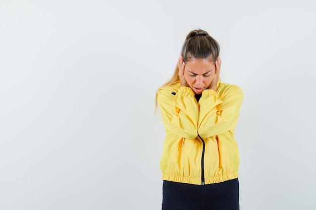 黄色のボンバージャケットと黒のズボンの若い女性が頬に手を置いて疲れ果てているように見える