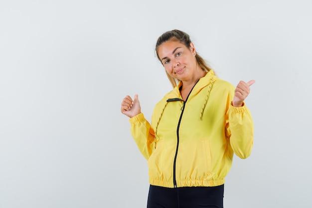 黄色のボンバージャケットと黒のズボンの若い女性は、二重の親指を上げて、かわいく見える