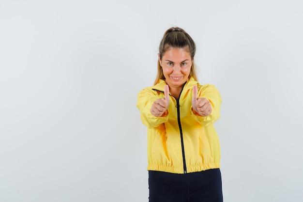 黄色のボンバージャケットと黒のズボンを着た若い女性が両手で親指を立てて、かわいく見える