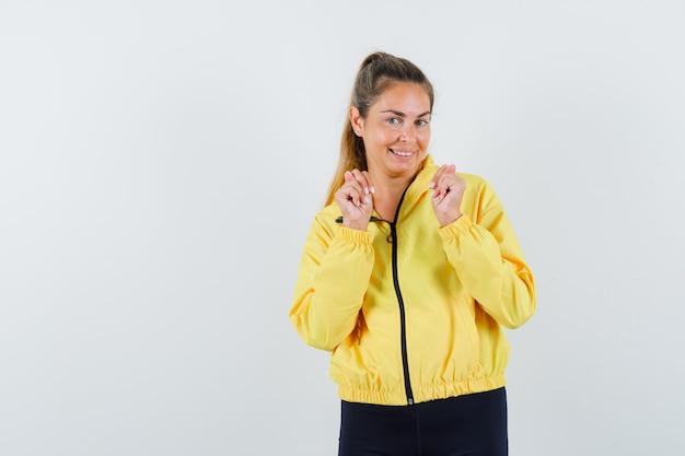黄色のボンバージャケットと黒のズボンの若い女性が勝者のジェスチャーを示し、かわいく見える