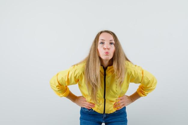 黄色のボンバージャケットとブルージーンズの若い女性が曲がり、腰に手をつないで、カメラにキスを送信し、楽観的な正面図を探しています。