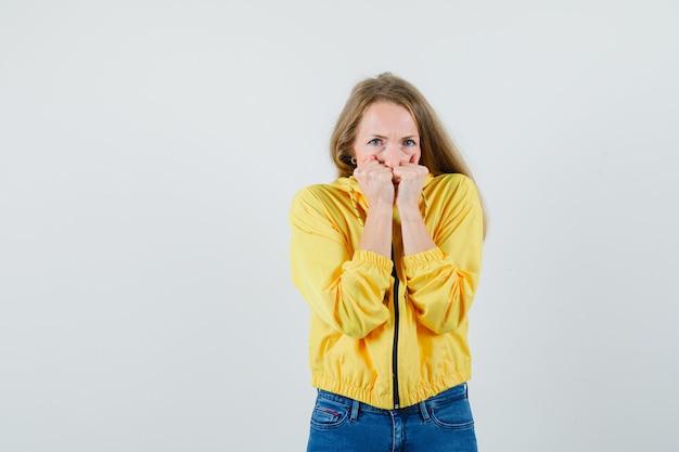 노란색 폭격기 재킷과 블루 진 감정적으로 주먹을 물고 매력적인, 전면보기를 찾고있는 젊은 여자.