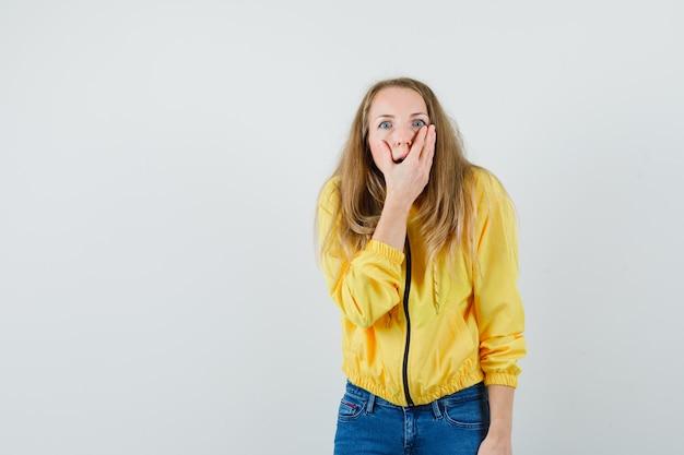 노란색 폭격기 재킷과 그녀의 입을 덮고 놀란, 전면보기를 찾고 블루 진에 젊은 여자.