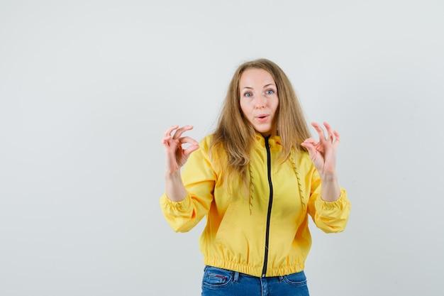 黄色のボンバージャケットとブルージーンズを着た若い女性が来て、楽観的に見える、正面図。