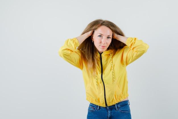 노란색 폭격기 재킷과 블루 진 머리에 손을 유지 하 고 매력적인, 전면보기를 찾고있는 젊은 여자.