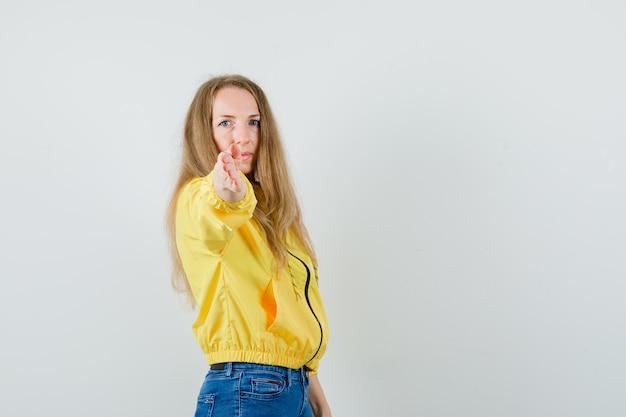 노란색 폭격기 재킷과 블루 진 카메라를 가리키고 심각한, 전면보기를 찾고있는 젊은 여자.