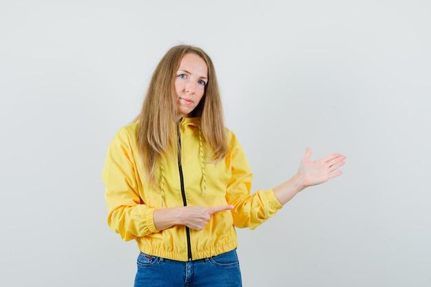 노란색 폭격기 재킷과 블루 진 오른쪽을 가리키고 자신감, 전면보기를 찾고있는 젊은 여자.