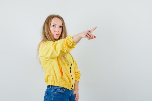 노란색 폭격기 재킷과 블루 진 오른쪽을 가리키고 낙관적, 전면보기를 찾고있는 젊은 여자.