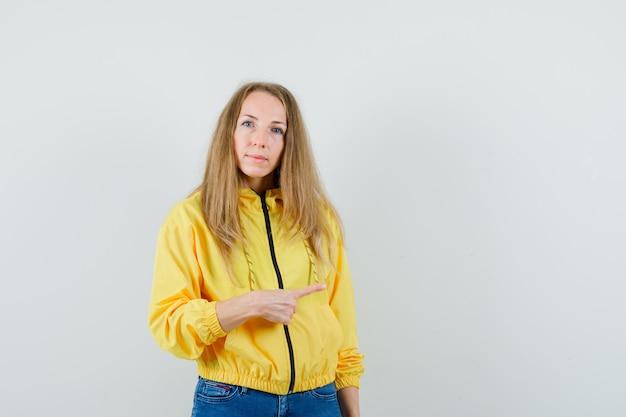 노란색 폭격기 재킷과 블루 진 오른쪽을 가리키고 심각한, 전면보기를 찾고있는 젊은 여자.