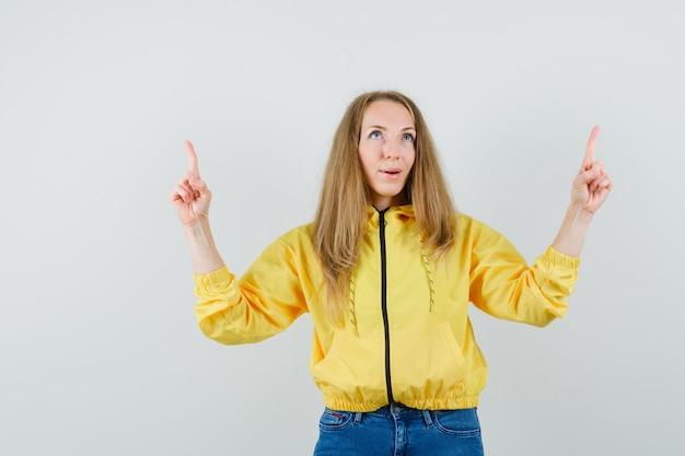 노란색 폭격기 재킷과 블루 진 가리키는 고 행복, 전면보기에서 젊은 여자.