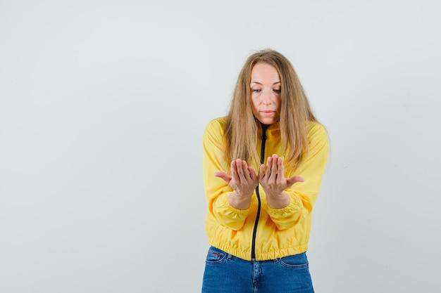 노란색 폭격기 재킷과 블루 진에 젊은 여자가 뭔가를 읽는 척하고 찾고