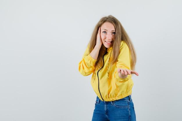 노란색 폭격기 재킷과 블루 진 뺨에 손을 댔을 젊은 여자