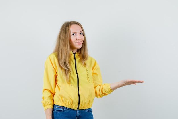 노란색 폭격기 재킷과 상상의 뭔가를 들고 손을 올리는 블루 진에 젊은 여자