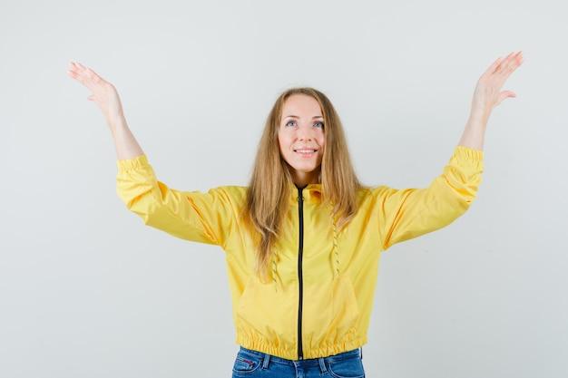 노란색 폭격기 재킷과 블루 진 손을 올리고 기쁨과 낙관적, 전면보기를 찾고 젊은 여자.