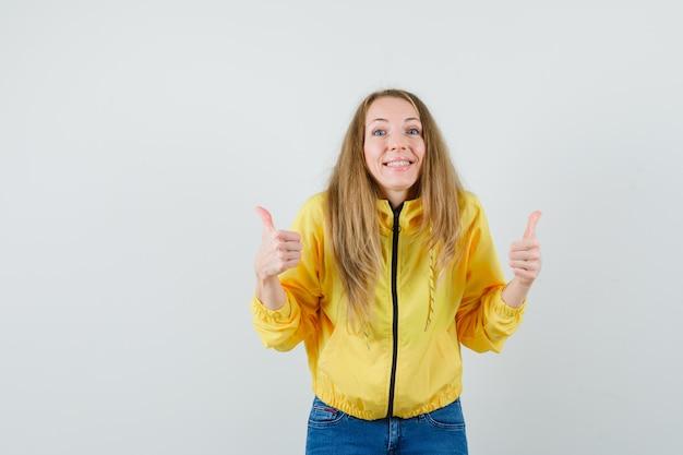노란색 폭격기 재킷과 두 엄지 손가락을 보여주는 블루 진에 젊은 여자와 낙관적, 전면보기를 찾고.