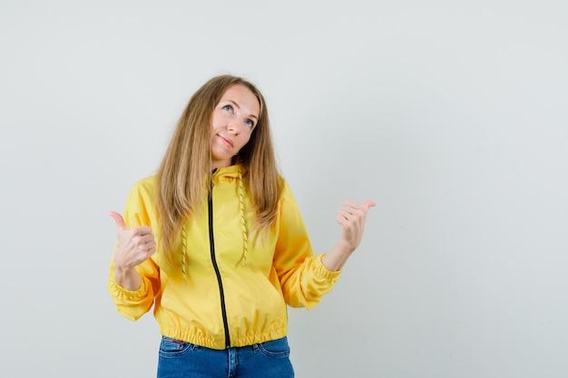 노란색 폭격기 재킷과 두 엄지 손가락을 보여주는 블루 진에 잠겨있는, 전면보기를 찾고 젊은 여자.
