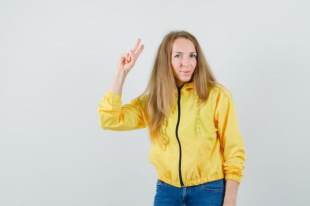 黄色のボンバージャケットとブルージーンズの若い女性が銃のジェスチャーを示し、楽観的に見える、正面図。