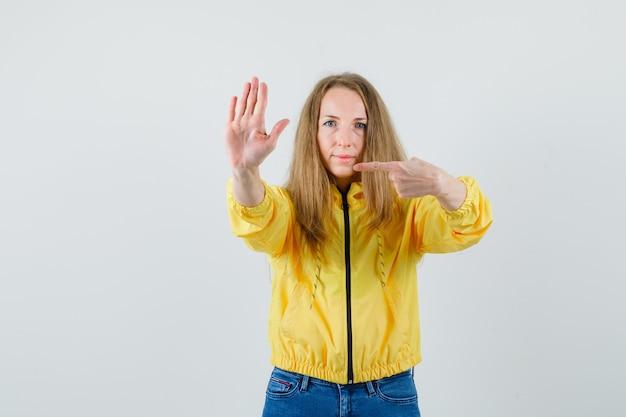 노란색 폭격기 재킷과 블루 진 정지 제스처를 표시하고 그것을 가리키고 심각한, 전면보기를 찾고 젊은 여자.