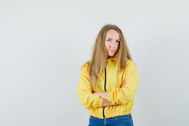 Молодая женщина в желтой куртке-бомбардировщике и синих джинсах стоит со скрещенными руками и позирует перед камерой и выглядит очаровательно, вид спереди.