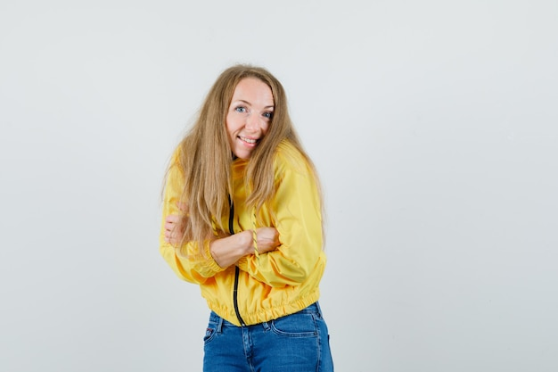 Молодая женщина в желтой куртке-бомбардировщике и синих джинсах, стоящая со скрещенными руками и позирующая перед камерой и выглядящая оптимистично, вид спереди.