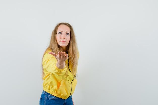 노란색 폭격기 재킷과 블루 진에 젊은 여자가 카메라에 손을 뻗어 놀란, 전면보기를보고.