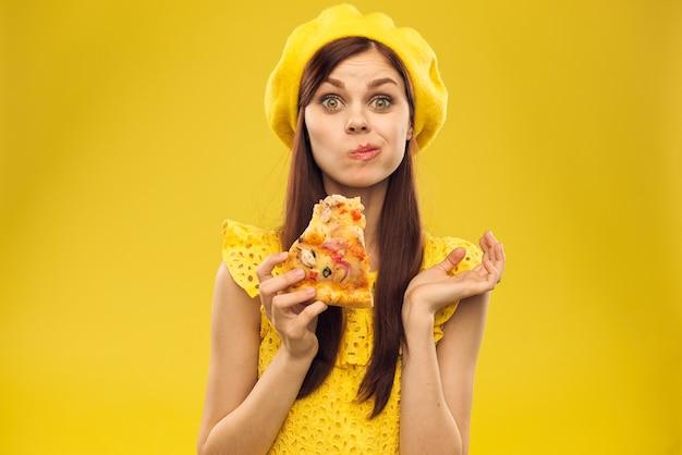 黄色い服を着た若い女性がピザを食べる