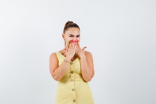 手のひらで口を覆い、混乱しているように見える黄色のドレスを着た若い女性、正面図。