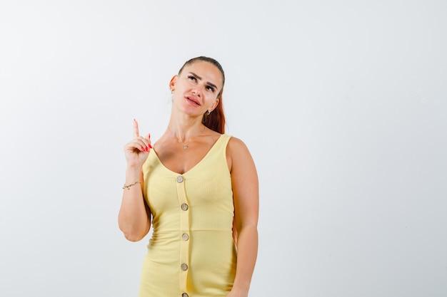 노란색 드레스를 가리키고 잠겨있는, 전면보기를 찾고있는 젊은 여자.