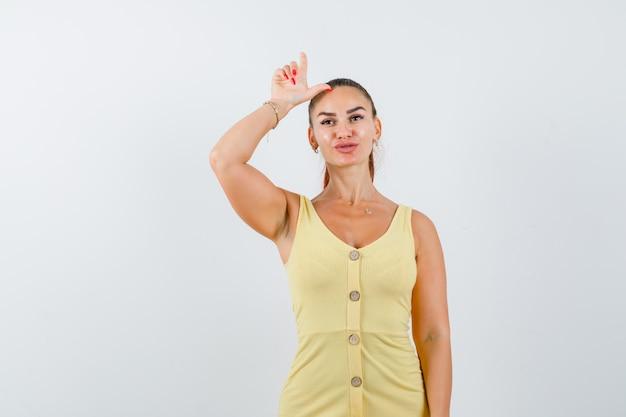 Молодая женщина в желтом платье показывает знак проигравшего над головой и задумчиво, вид спереди.