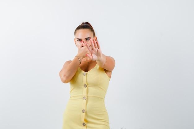 Молодая женщина в желтом платье показывает жест стоп, прикрывает ладонью и выглядит испуганной, вид спереди.