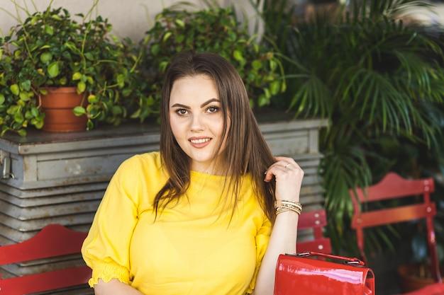 노란 드레스에 젊은 여자는 거리 식당에서 테이블을 앉아