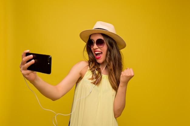 Молодая женщина в желтом платье с шляпой и солнцезащитными очками, смотрит видео