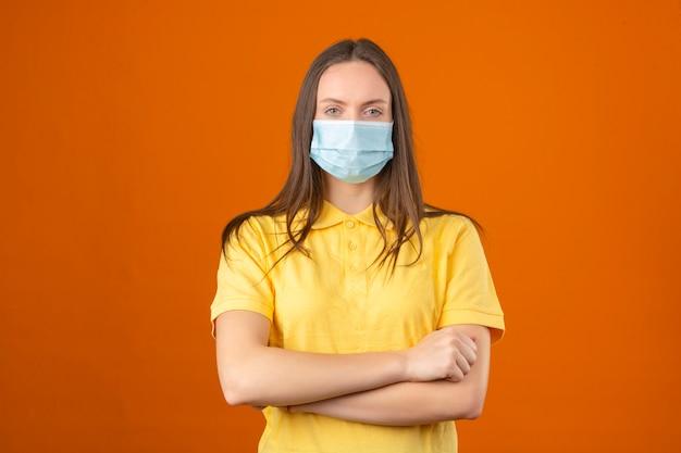 노란색 폴로 셔츠와 의료 보호 마스크 손에 젊은 여자는 오렌지 배경에 그녀의 가슴에 넘어