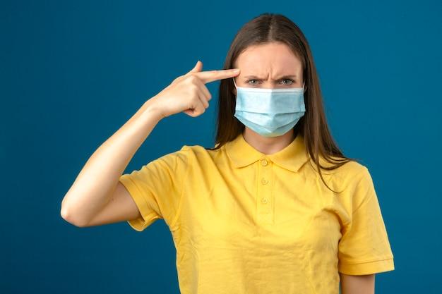 黄色のポロシャツと青色の背景に分離された深刻な顔で彼女の頭に指を指して医療用防護マスクの若い女性