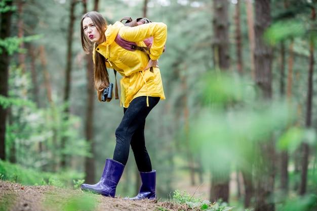 숲을 여행하는 동안 무릎 통증을 느끼는 데 어려움을 겪는 노란색 비옷을 입은 젊은 여성