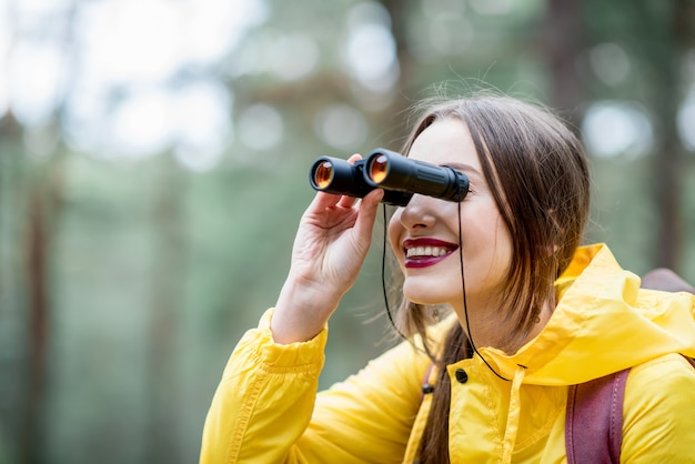 緑の松林で双眼鏡とバックパックと黄色のレインコートハイキングの若い女性