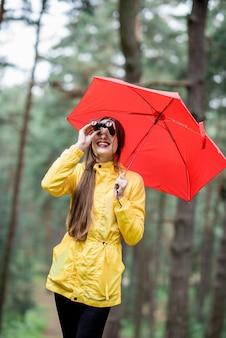 Молодая женщина в желтом плаще, походы с биноклем и красным зонтиком в сосновом лесу