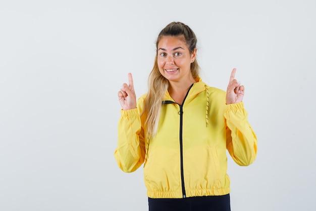 노란색 우비를 가리키고 기쁘게 찾고있는 젊은 여자