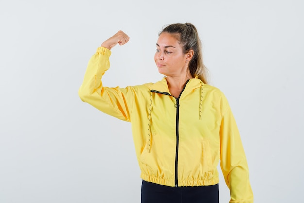 Молодая женщина в желтом плаще показывает мышцы рук и выглядит уверенно