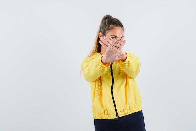 노란색 우비에 젊은 여자 교차 손으로 중지 제스처를 보여주는 심각한 찾고