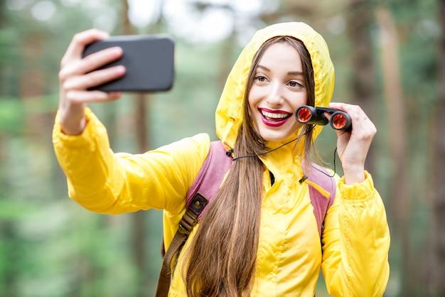 緑の森で双眼鏡とバックパックでハイキングしながら自分撮りの肖像画を撮る黄色のレインコートの若い女性