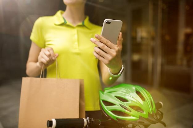 街の通りで注文を追跡するためにガジェットを使用してパッケージを配信する黄色いシャツの若い女性。支払いを受け取り、配送先住所を追跡するためにオンラインアプリを使用する宅配便。現代のテクノロジー。