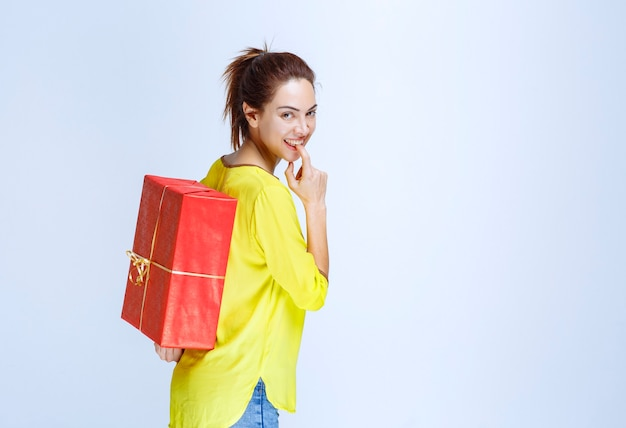 Молодая женщина в желтой рубашке прячет за собой красную подарочную коробку
