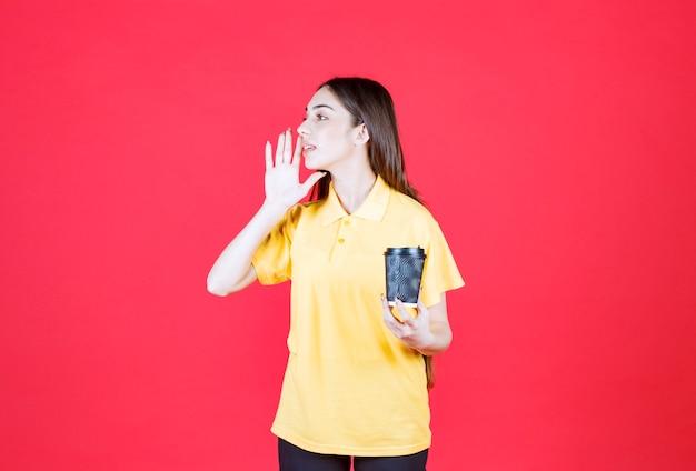 黒の使い捨てコーヒーカップを保持し、誰かを呼び出す黄色のシャツの若い女性