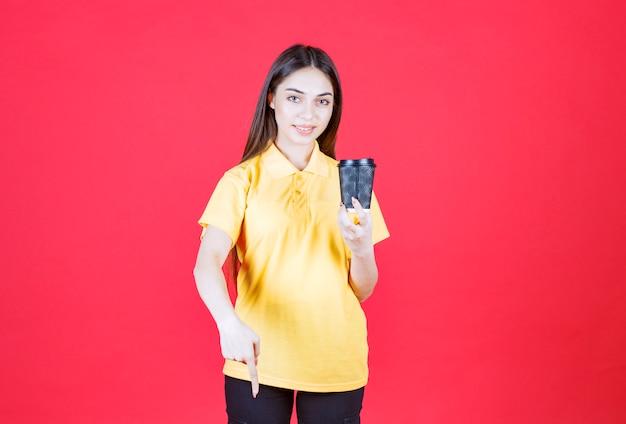 黒の使い捨てコーヒーカップを保持し、彼女のパートナーを共有するように招待している黄色いシャツの若い女性