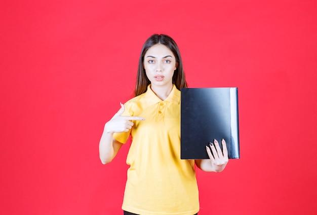 검은 폴더를 들고 긍정적인 손 기호를 보여주는 노란색 셔츠에 젊은 여자