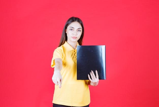 노란색 셔츠를 입은 젊은 여성이 검은색 폴더를 들고 동료를 가리키며 전화를 걸고 있습니다.